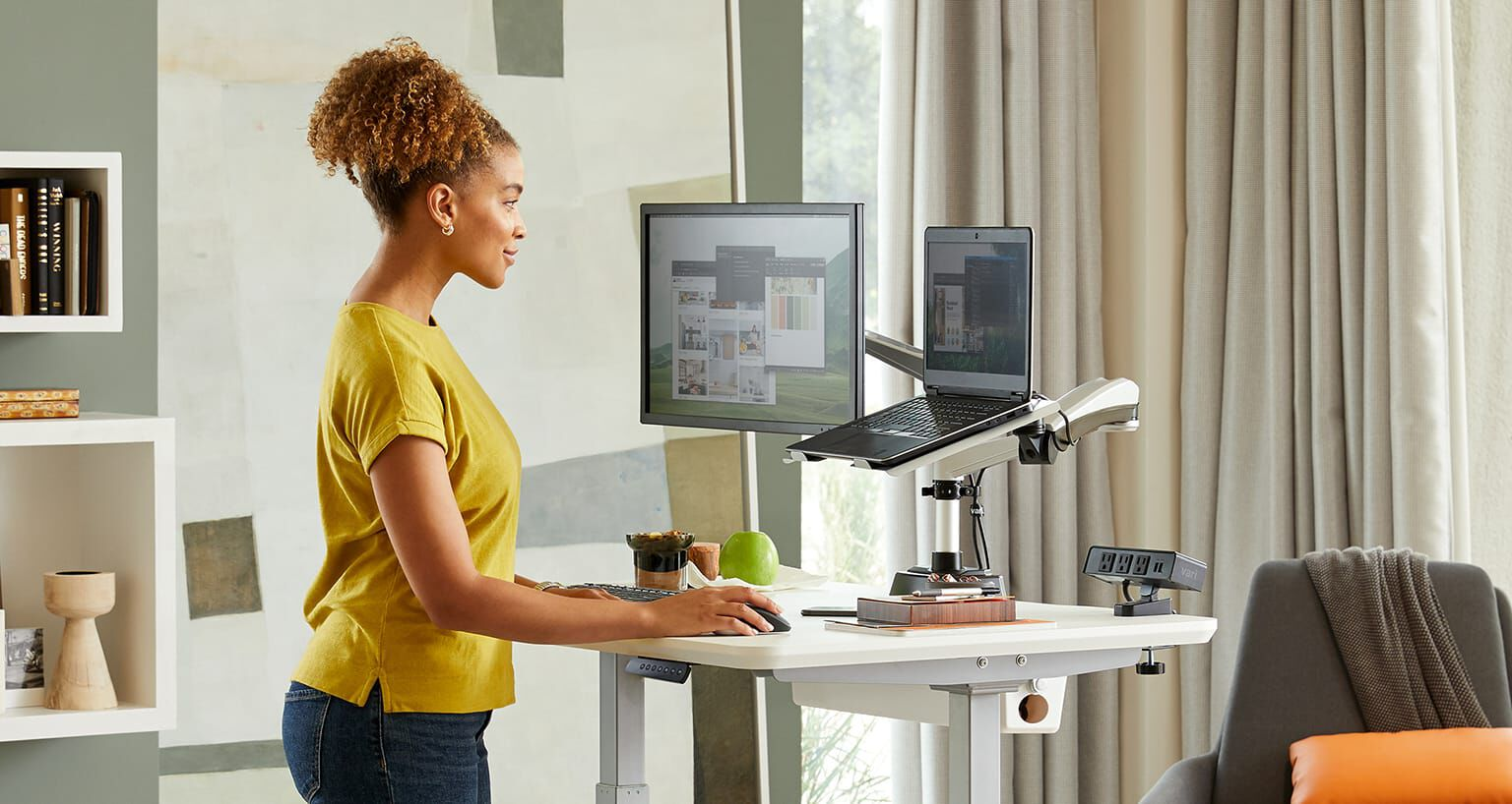 Vari Electric Standing Desk with monitor arm and laptop stand in home office