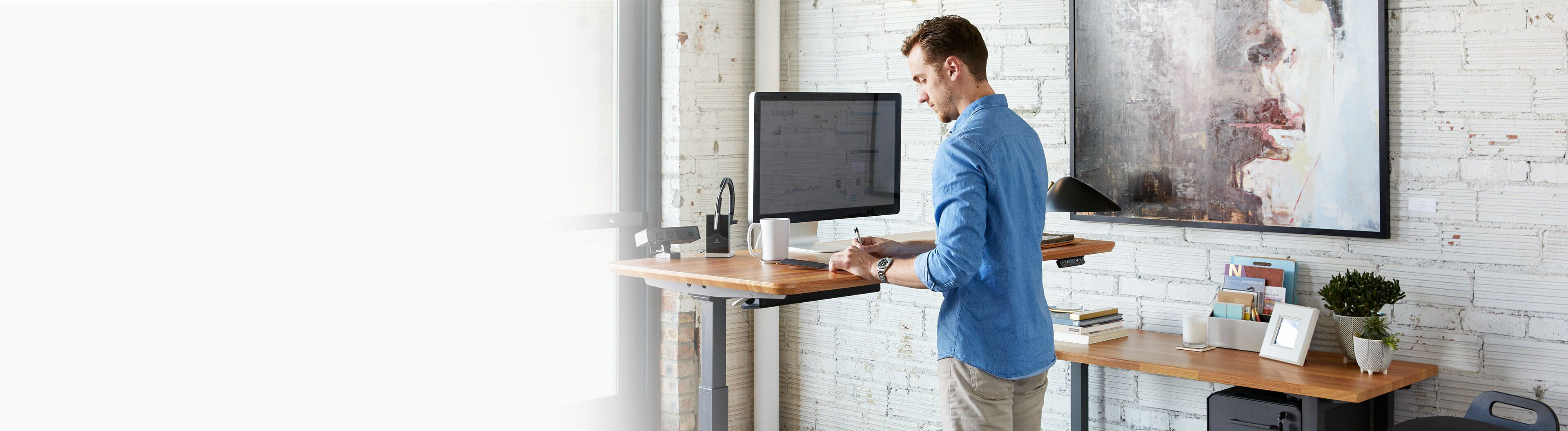 professional working at electric standing desk in a home office