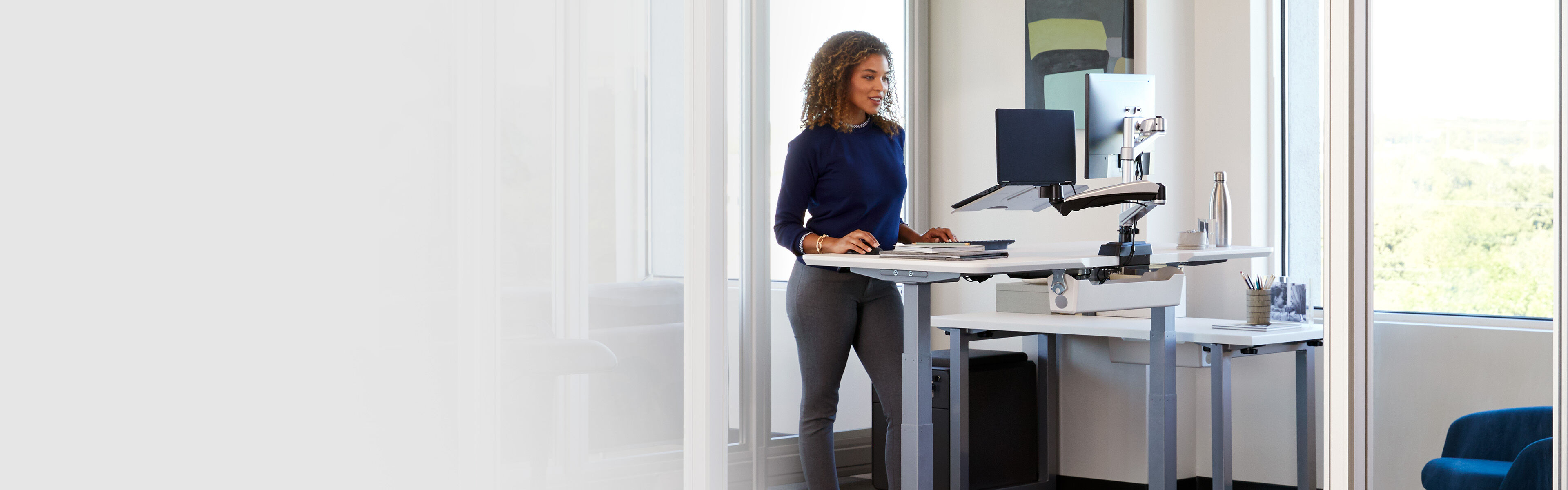 professional working at electric standing desk in office setting