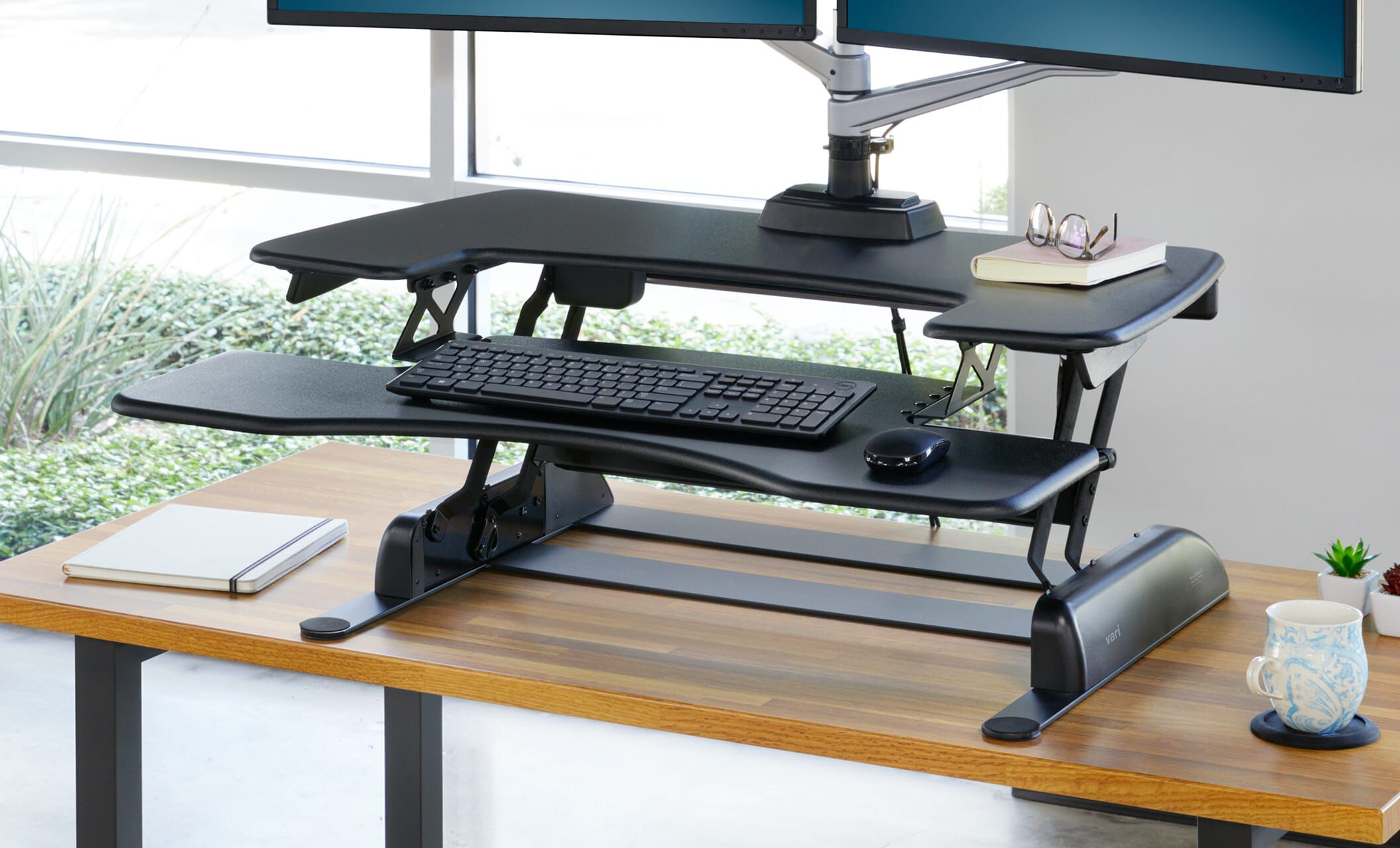 Desk riser has been lifted to a standing position to feature the weighted base and keyboard tray