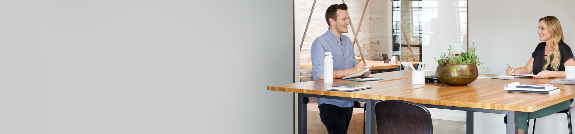 three coworkers collaborate in a conference room comprised of Vari products