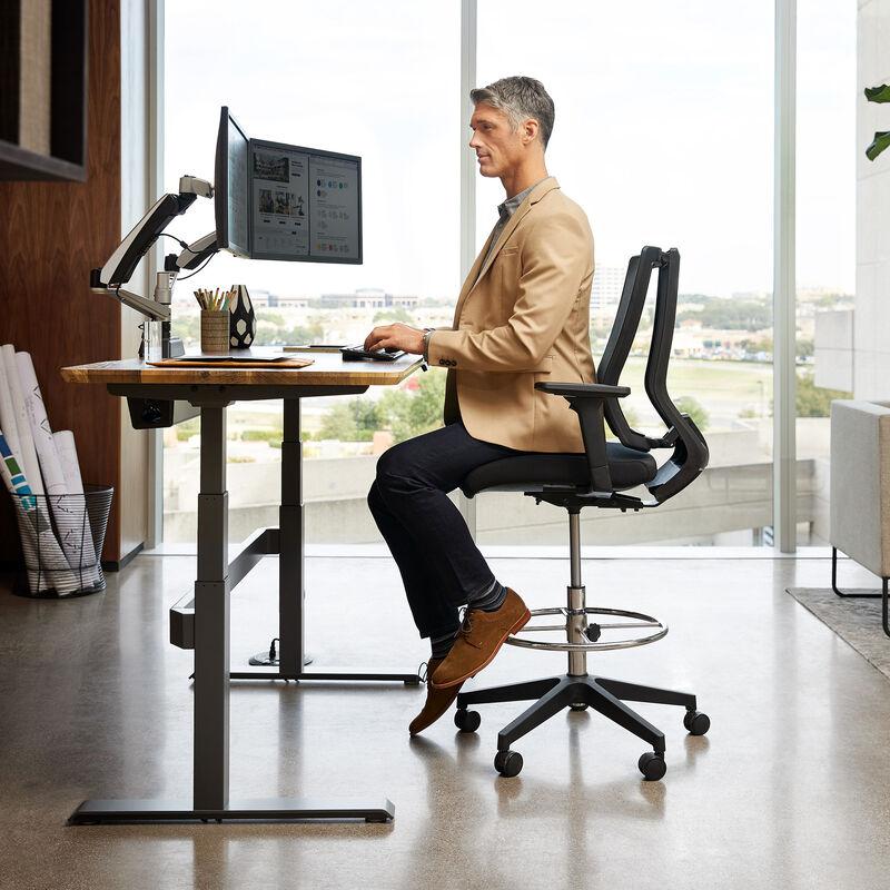 individual seated in vari drafting chair image number null