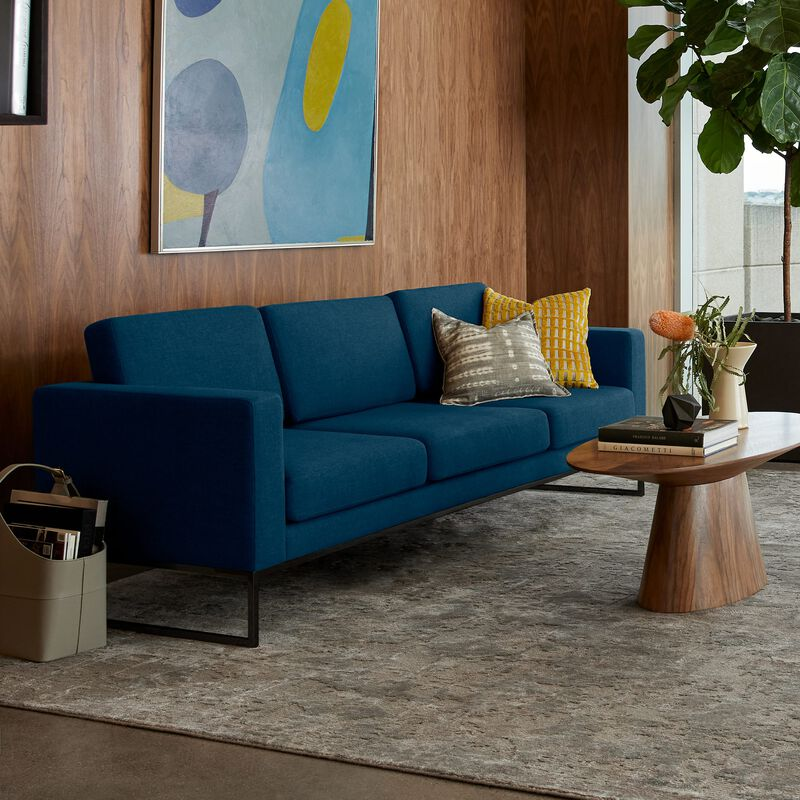 navy three-seat sofa sits in office space to create additional seating image number null