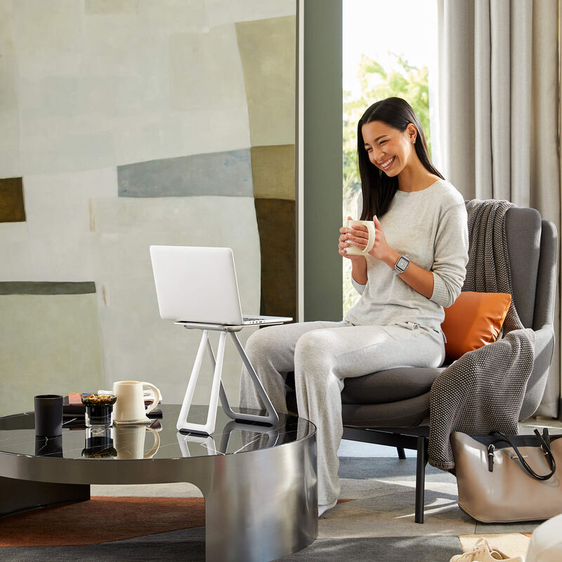 professional seated in living room with portable laptop stand on coffee table propping up laptop image number null