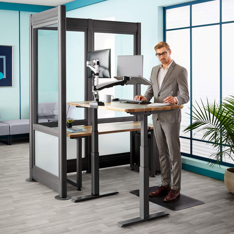 professional works at electric standing desk in silver private office  image number null