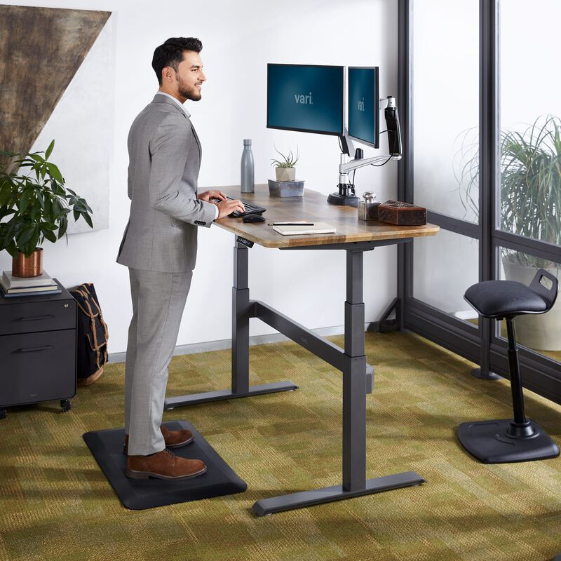 Professional working at Electric Standing Desk 60x30 Reclaimed Wood in raised position at office image number null