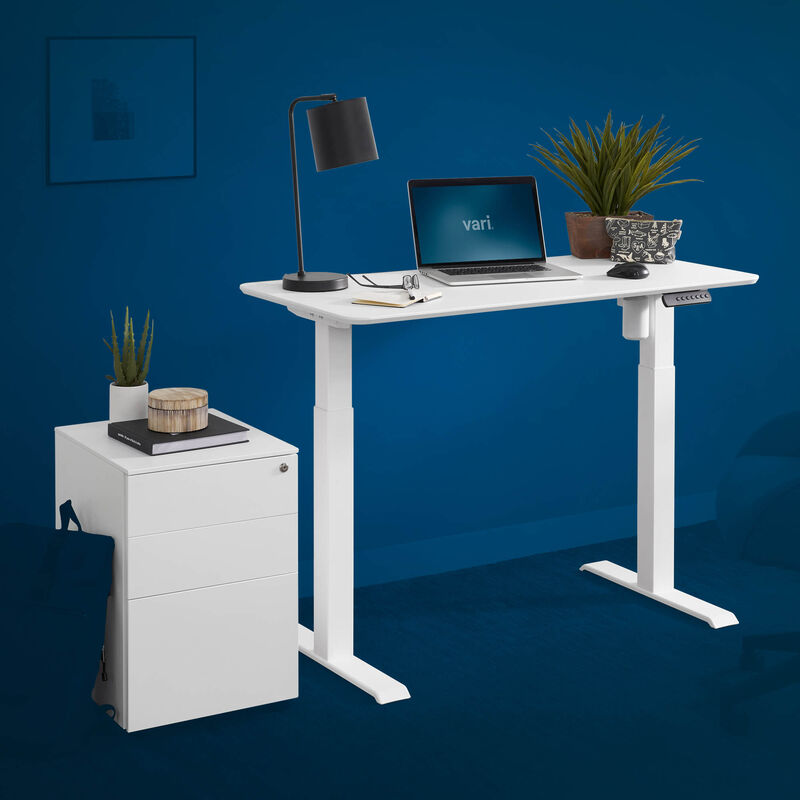 Essential electric standing desk 48 by 24 and an essential file cabinet in white are shown on a blue background image number null