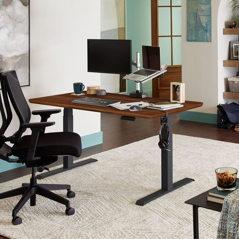 Electric Standing Desk 60x30 Dark Wood in lowered position at home image number null
