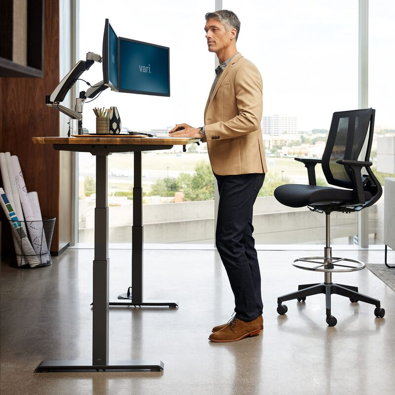 Professional standing at Electric Standing Desk 60x30 reclaimed wood in raised position at office image number null