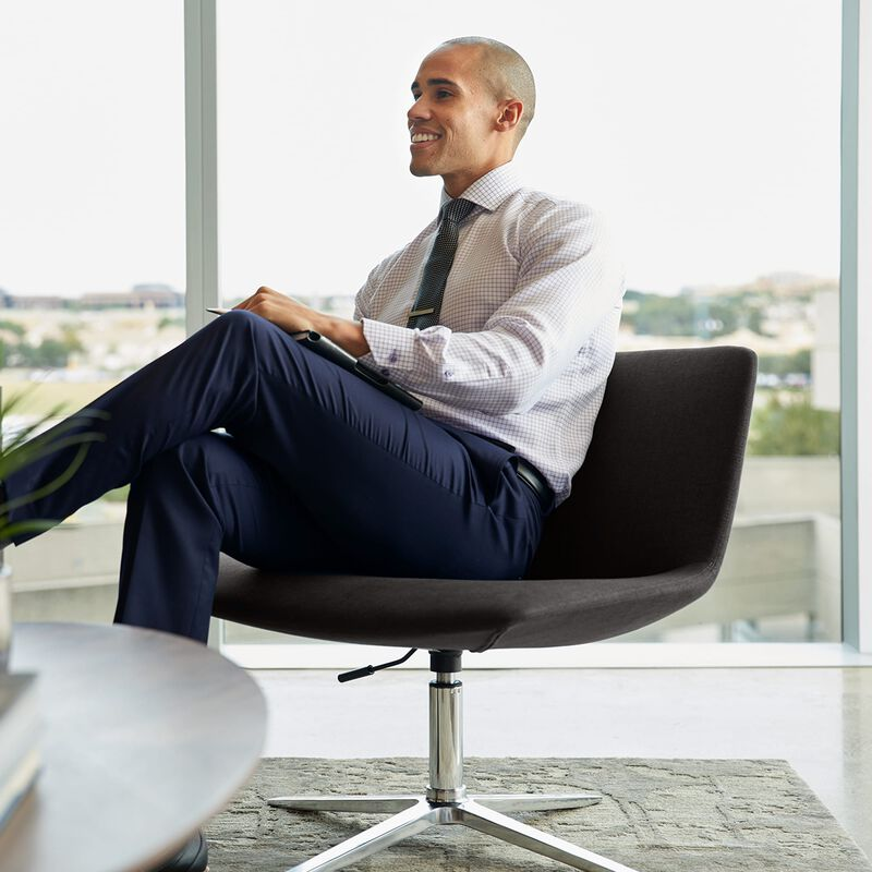 professional seated in deep grey lounge chair in office setting image number null