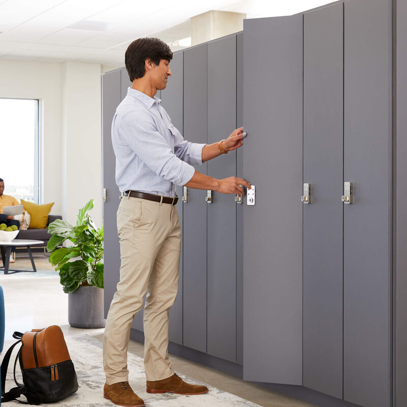 individual placing belongings inside storm grey locker in office setting image number null
