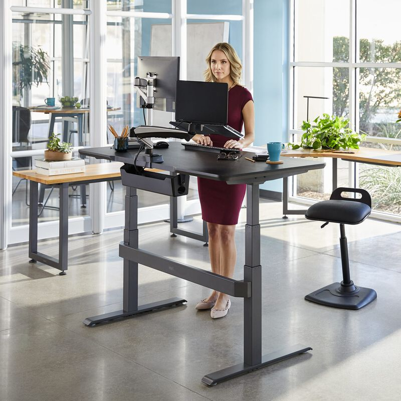 Professional working at Electric Standing Desk 60x30 Black in raised position at office image number null