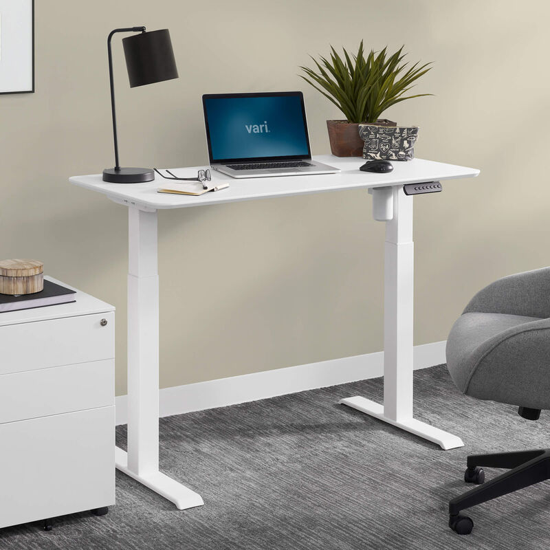 vari essential electric standing desk in white in office setting image number null