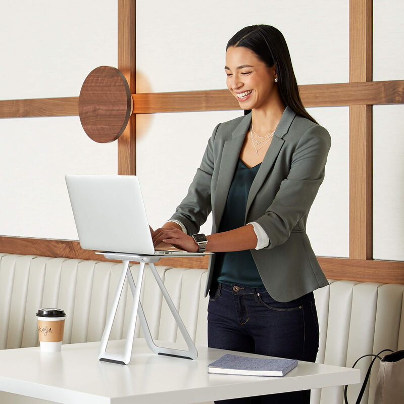 professional with laptop mounted on portable laptop stand in cafe  image number null