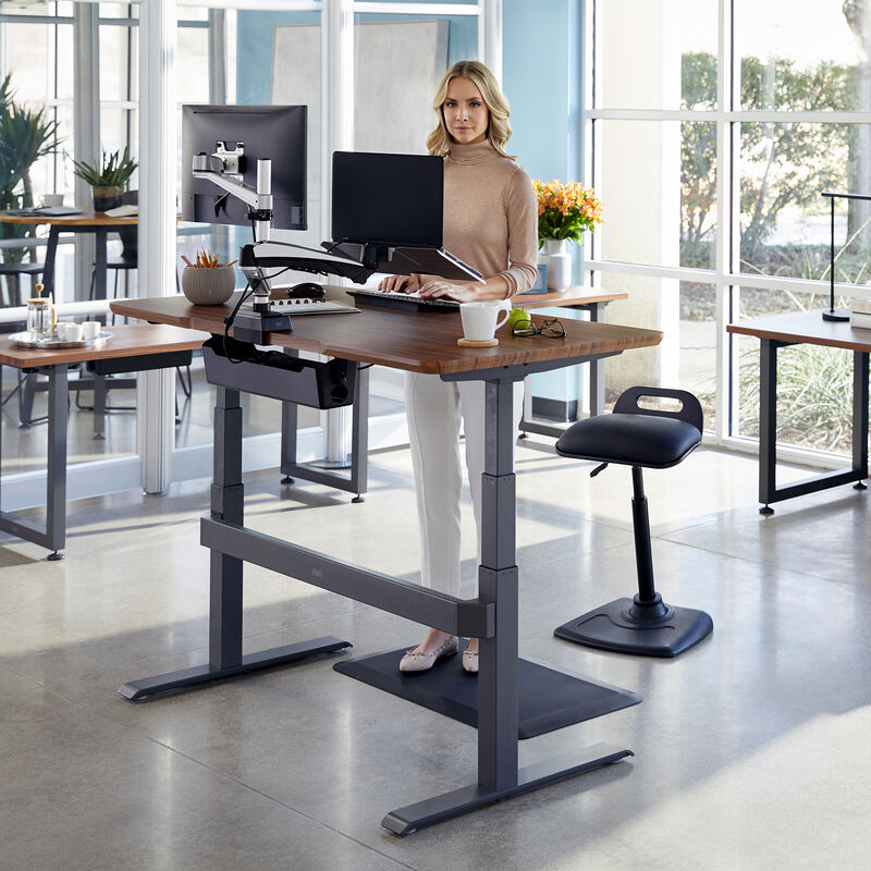Professional working at Electric Standing Desk 60x30 Darkwood in raised position at office image number null
