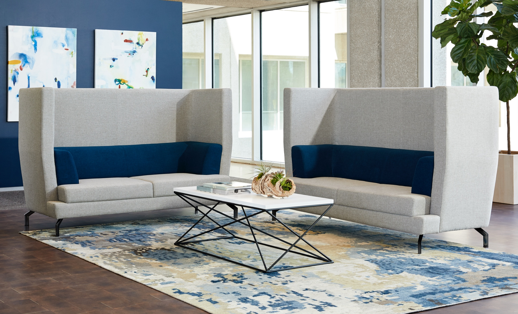 two high back sofas surround a coffee table in an office setting