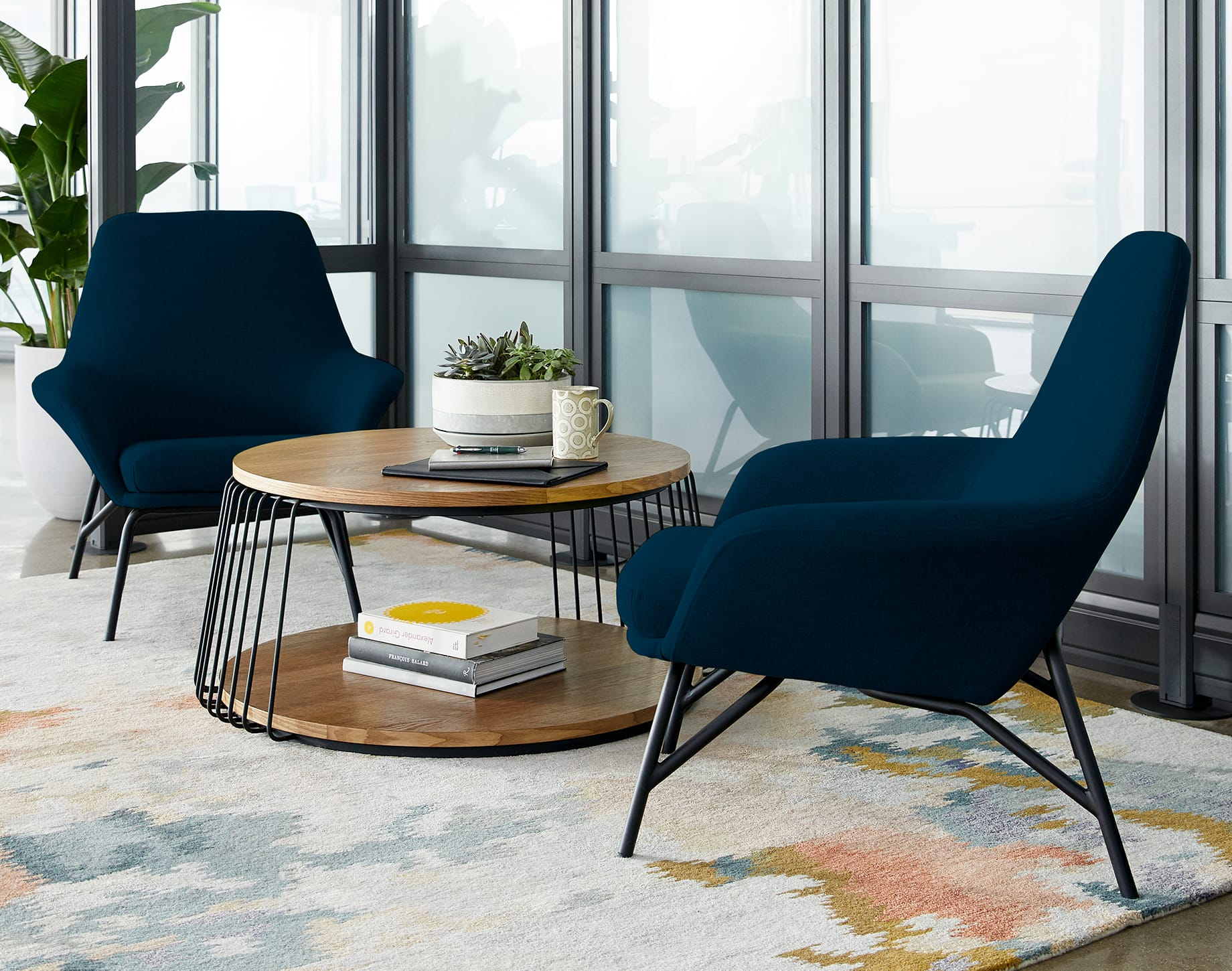 two chairs in navy are positioned around a coffee table
