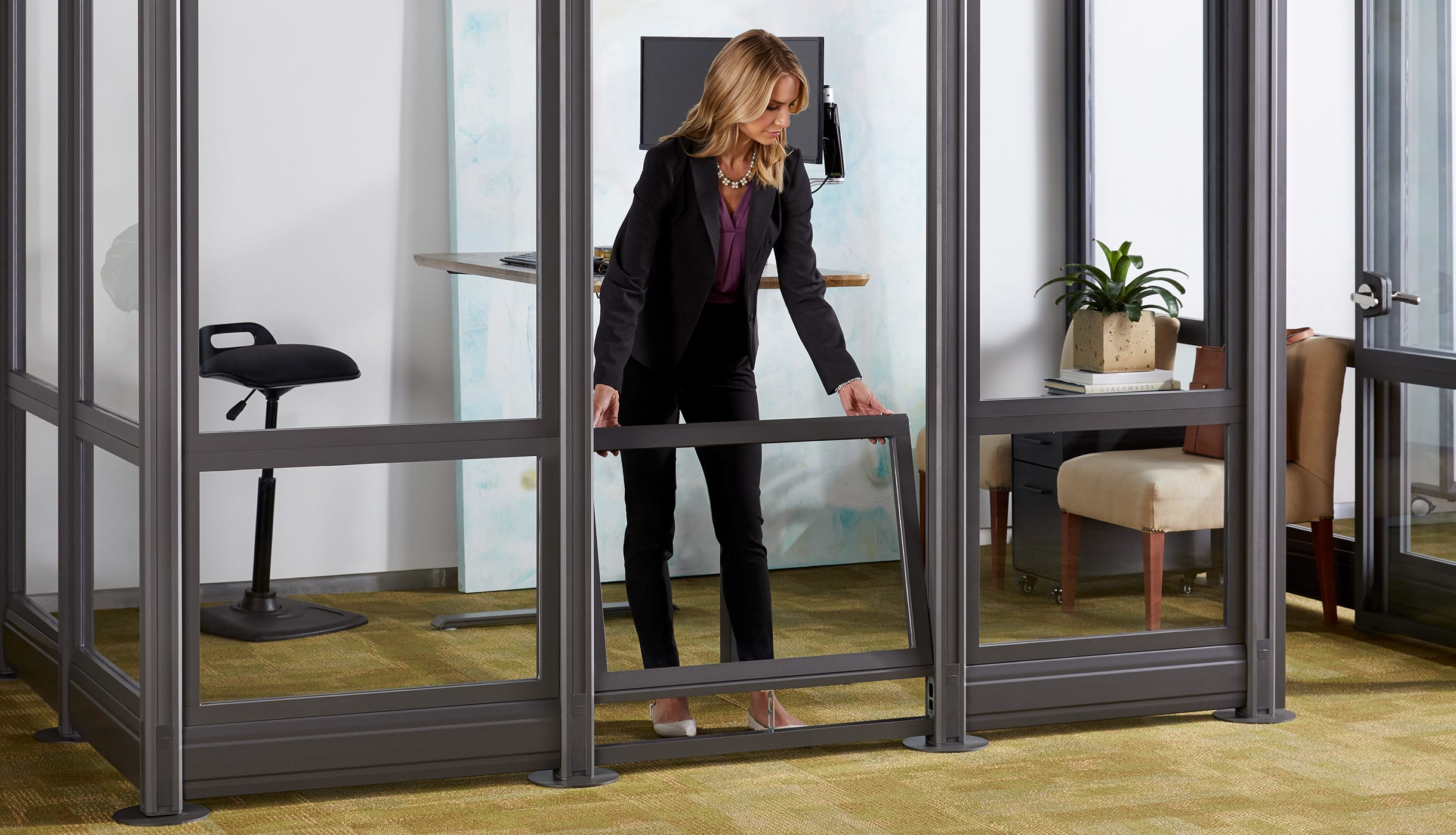 professional in business casual attire places wall panel into its slot as she finishes building her private office