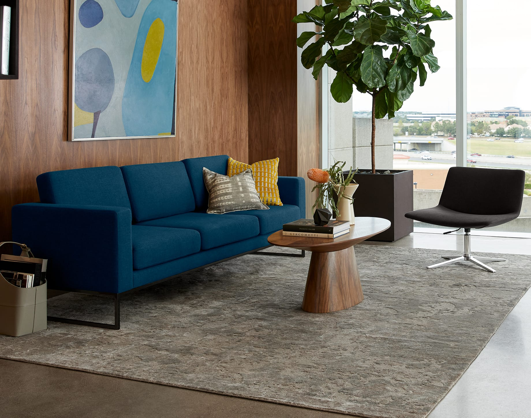 three-seat sofa appears with grey chair and oval coffee table in office space