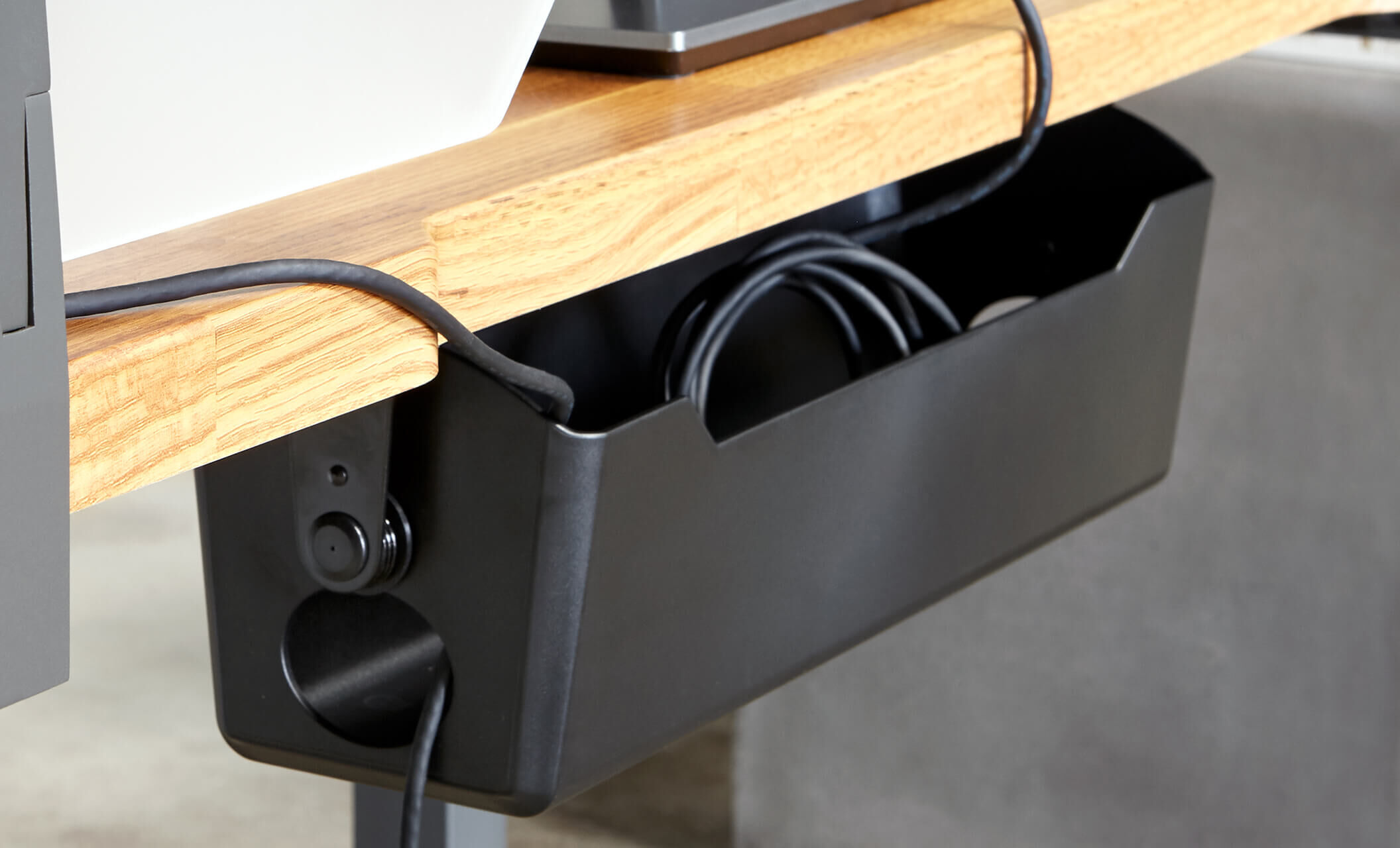 black cable management tray attached to desk in office setting