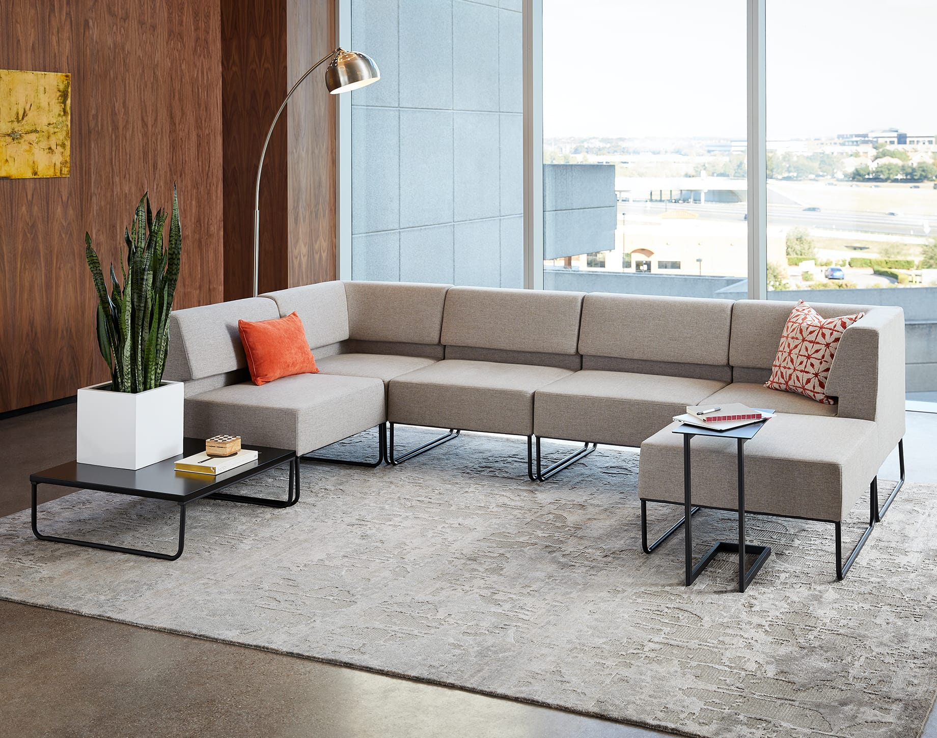 grey sectional sofa appears in office with variety of side and coffee tables