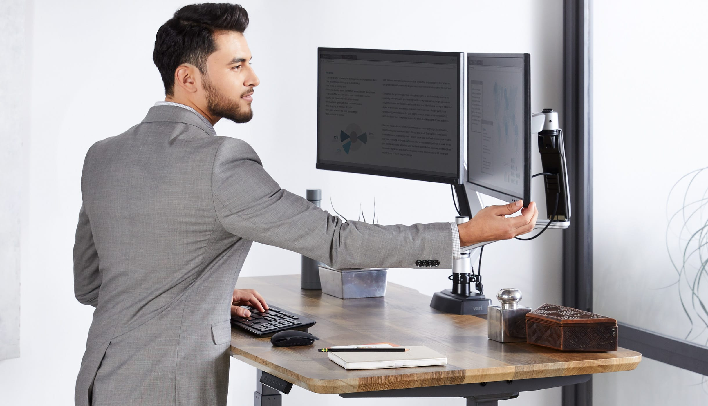 professional adjusts his monitors easily with one hand to ensure it's properly placed for the best posture.