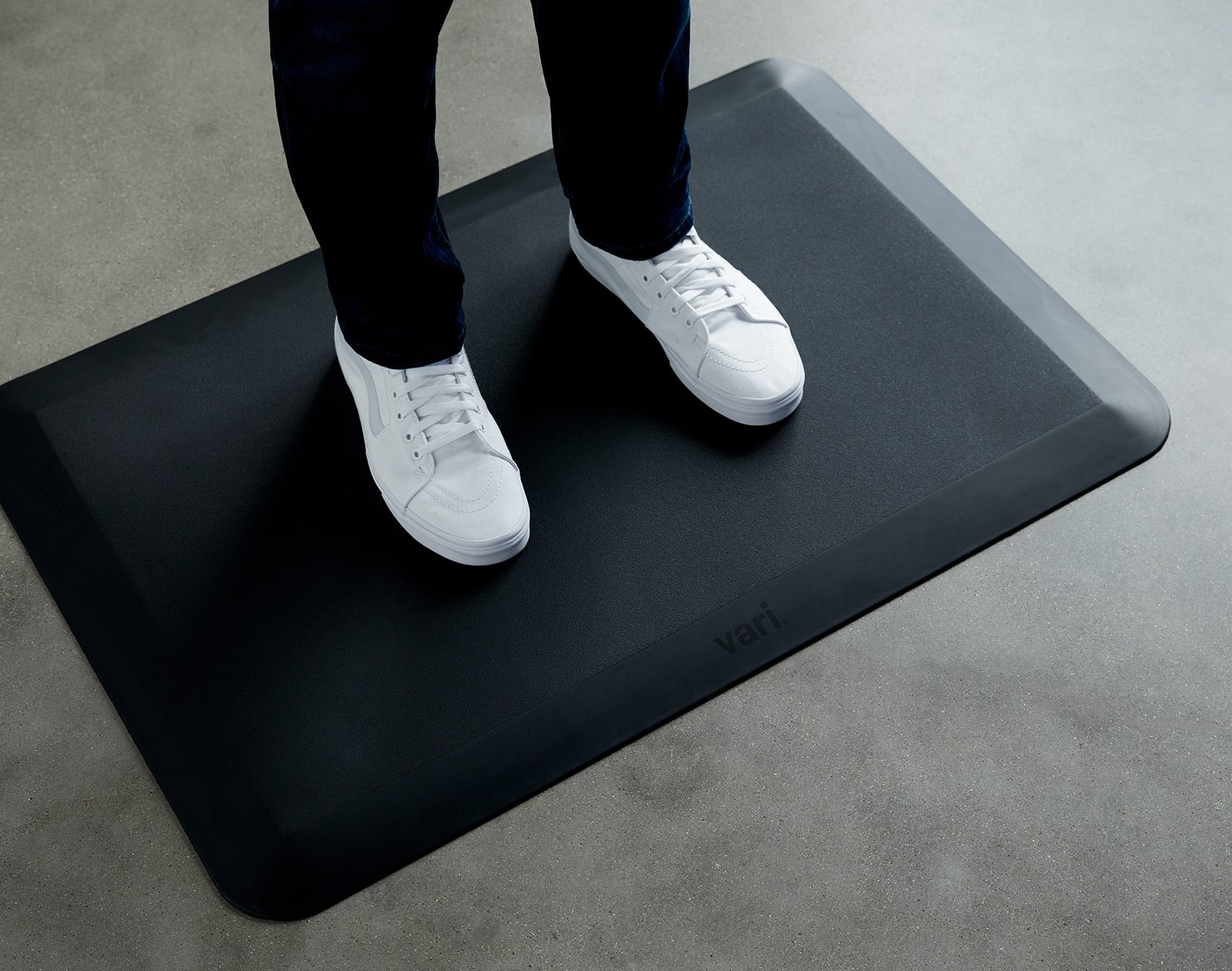 two feet on a standing mat in sneakers