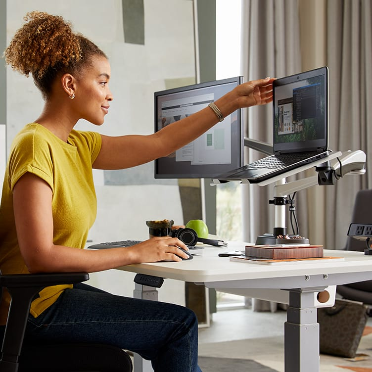 professional seated at electric standing desk adjusting mounted laptop