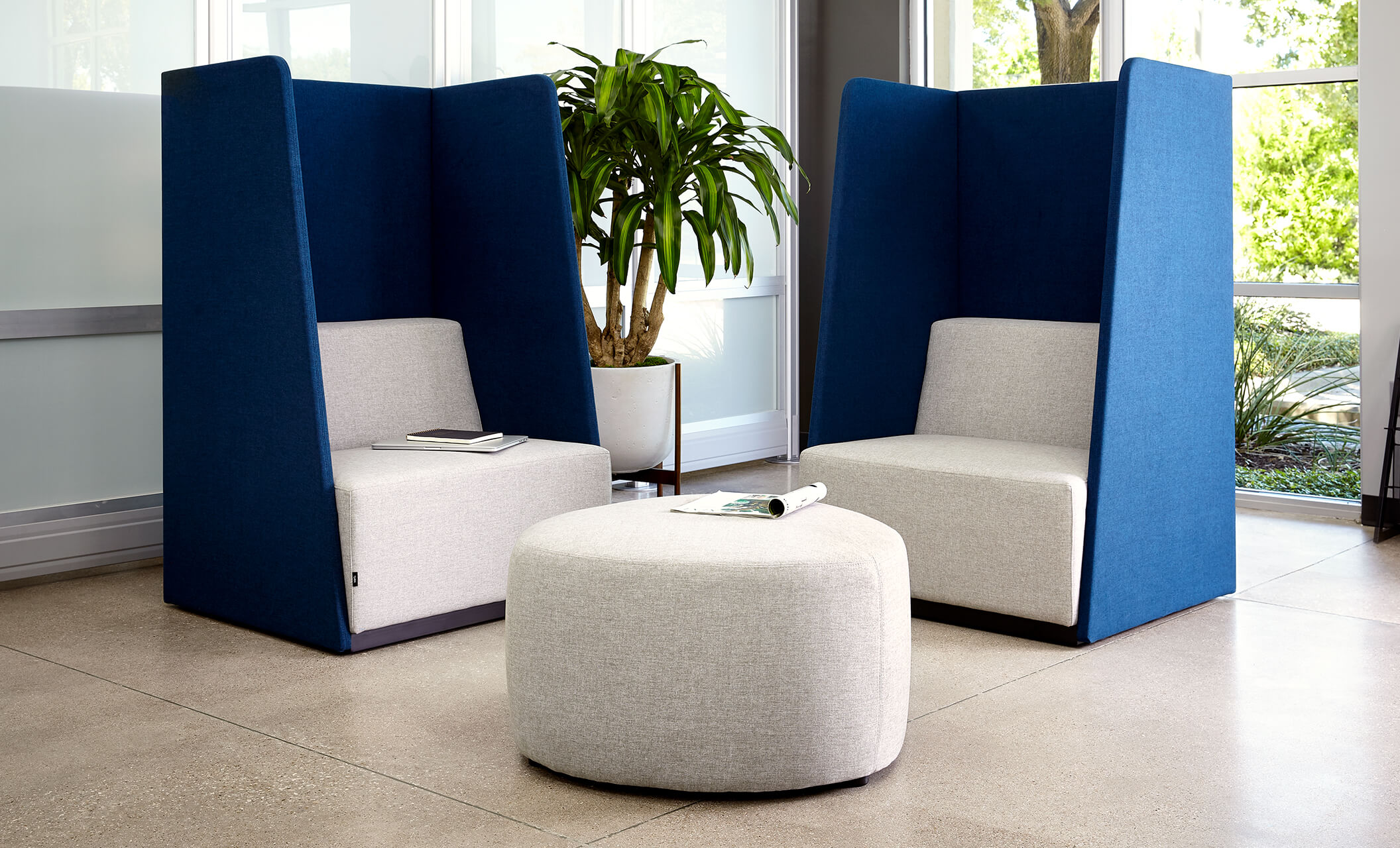 two high back chairs appear with a small ottoman in an office environment