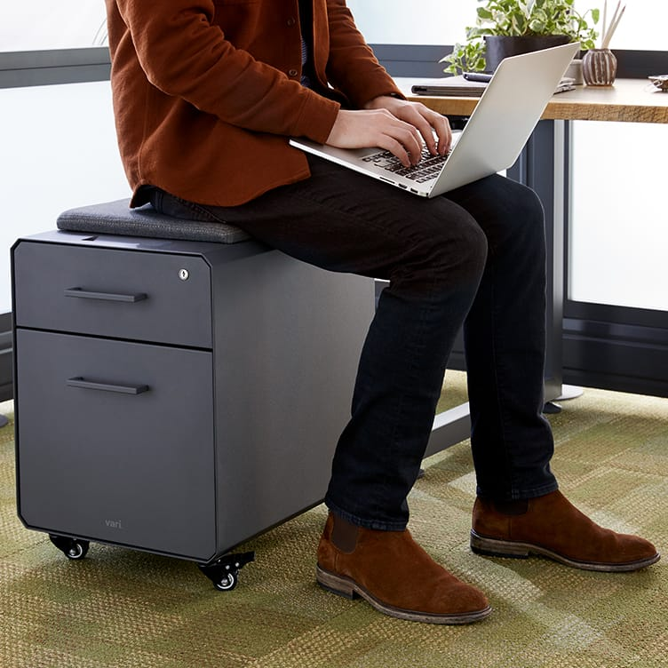 professional seated on storage seat while working on laptop