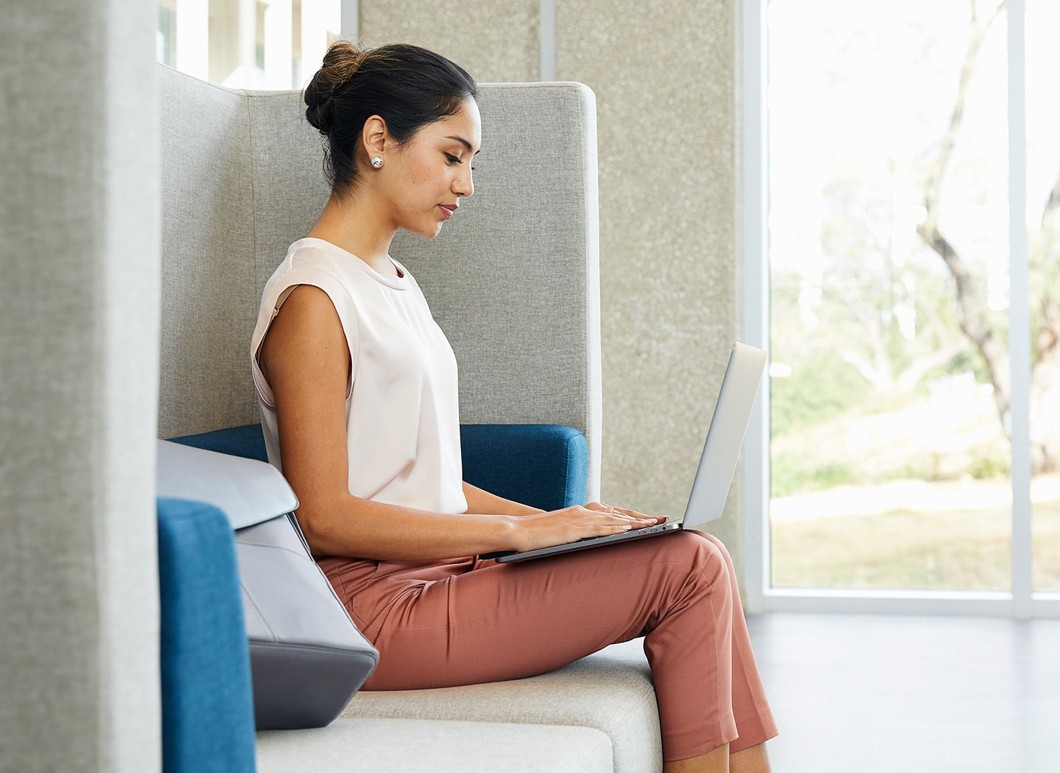 professional sits on soft seating and works on a laptop