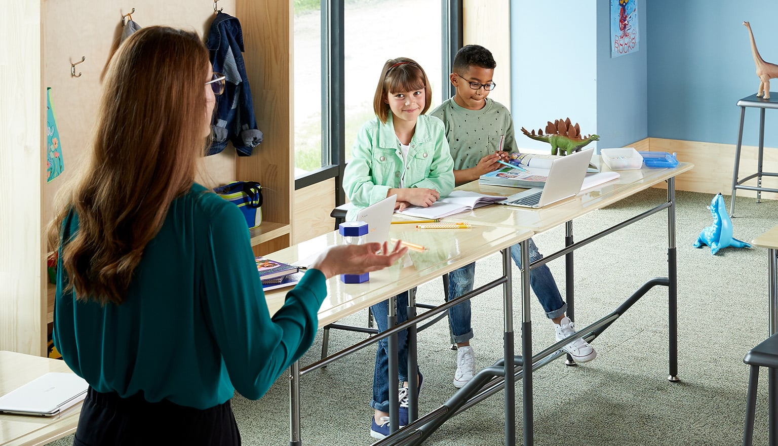 young students engage with teacher while standing at their school desks