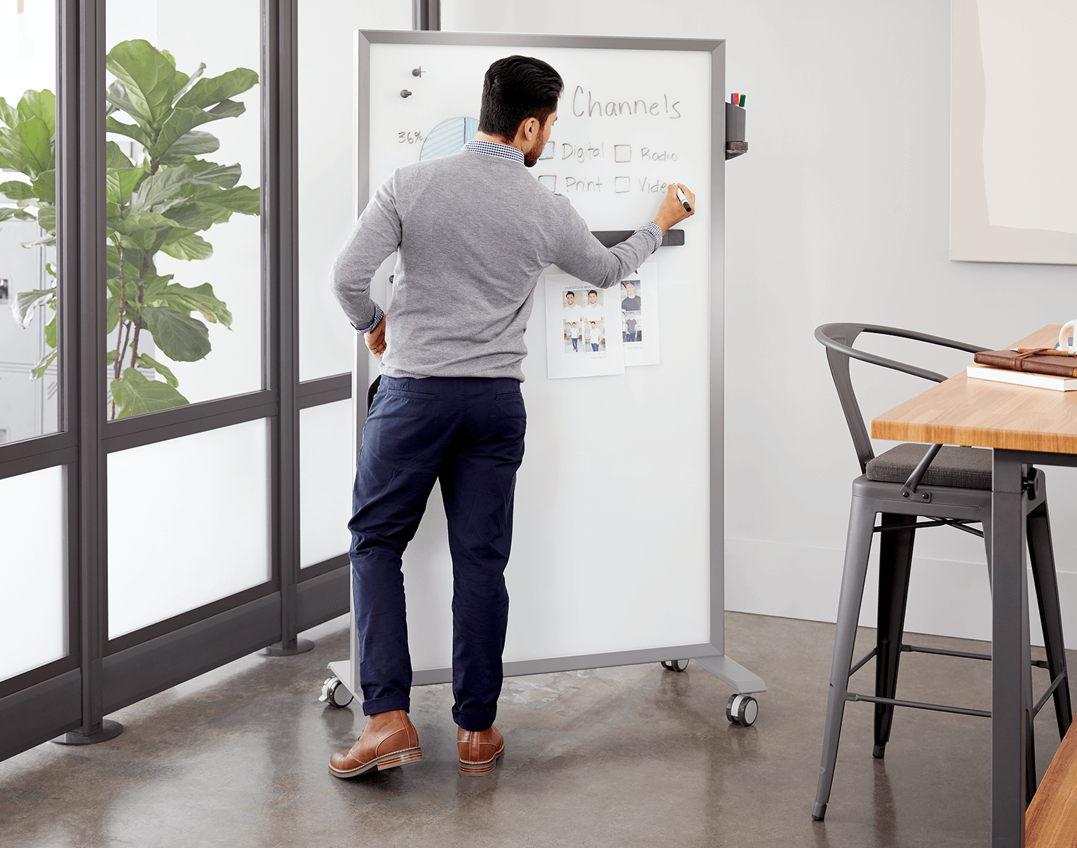 man writes on a markerboard to present data in a meeting