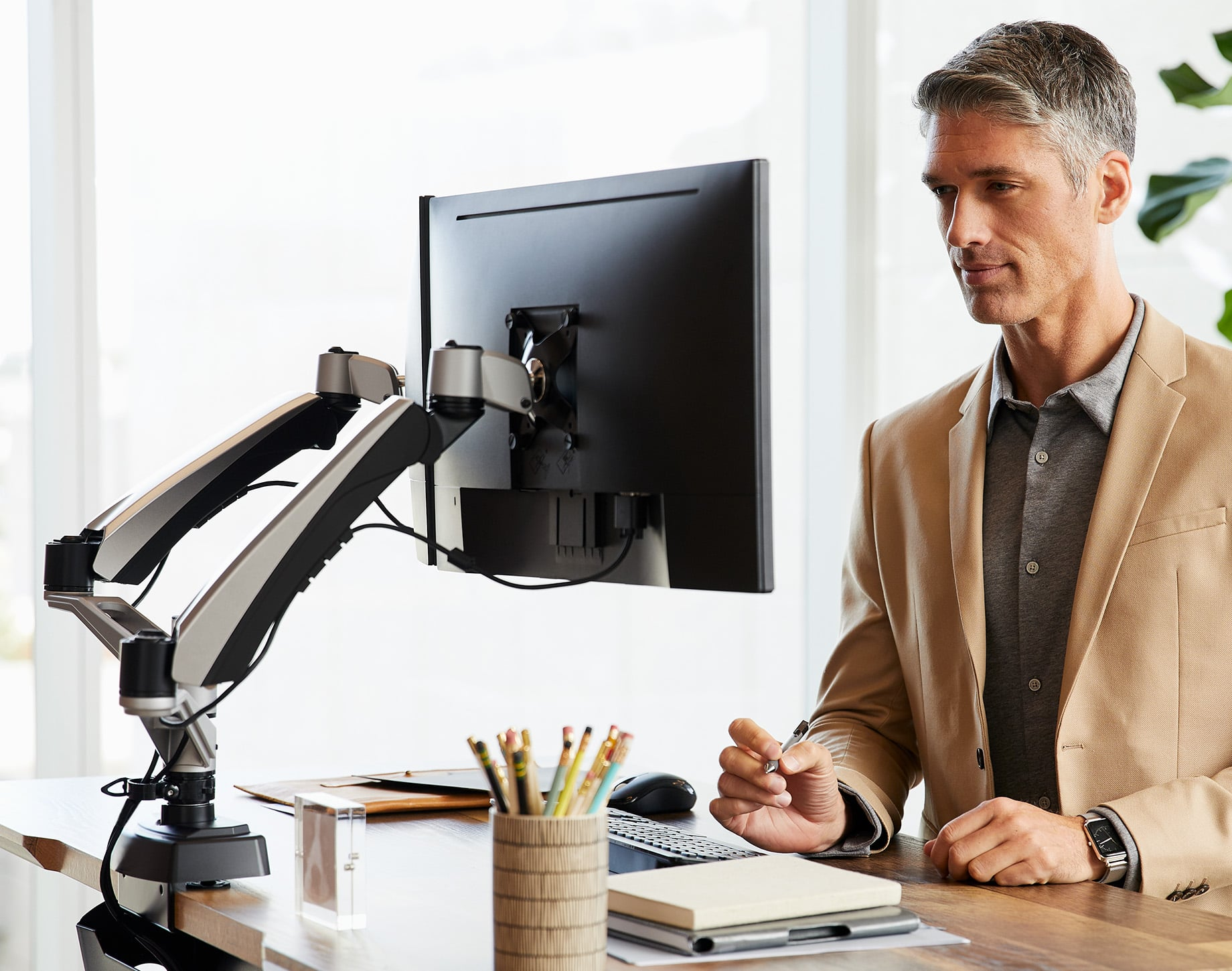 adjustable monitor arms hold computers high enough so that an office professional can comfortably use the computer