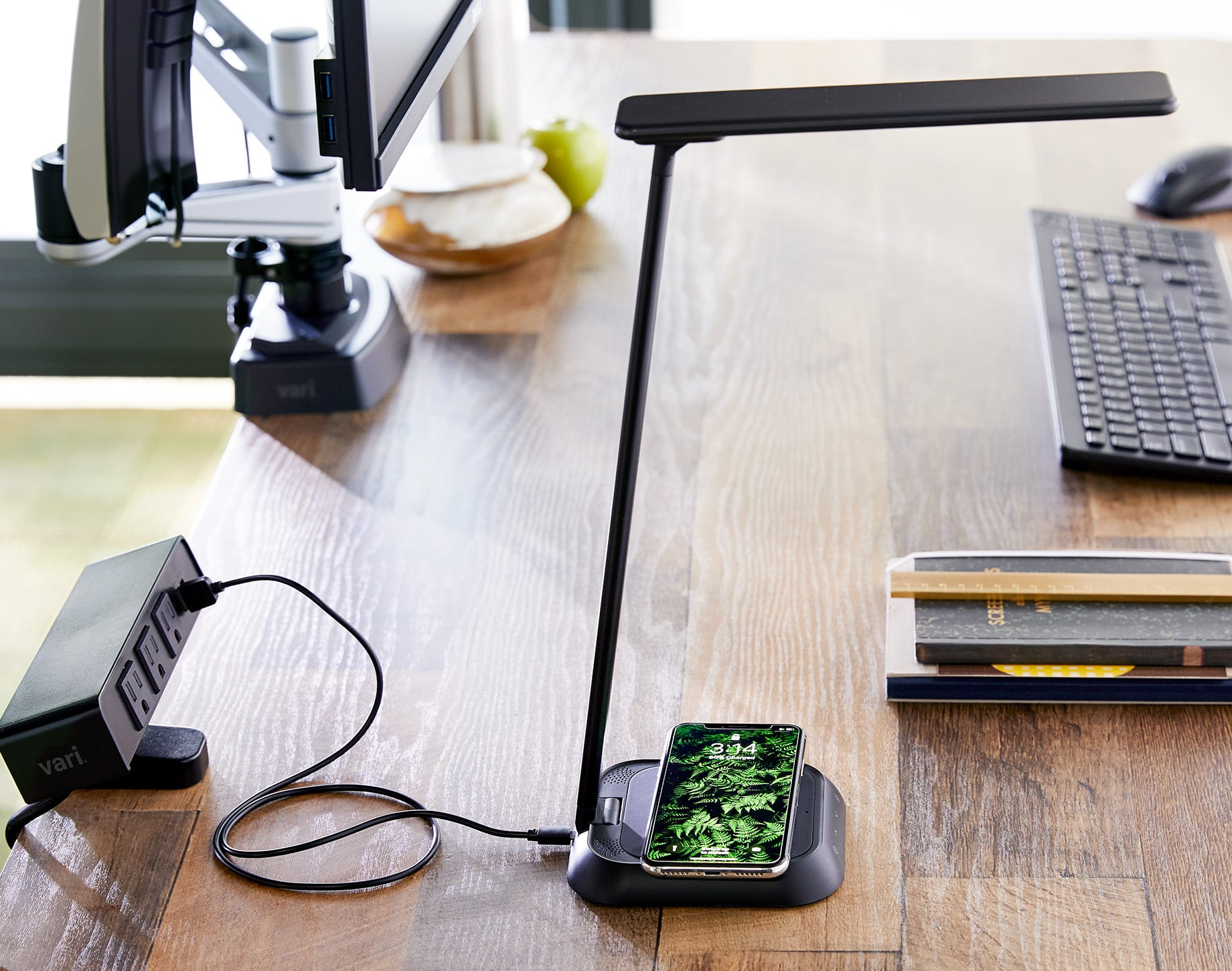 a lamp shines light on a functioning desk and wirelessly charges a smartphone. the light is plugged into a powrerhub, conviently clamped on to the desk.